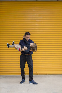 Happy father carrying son at yellow roller shutter - MAUF02103