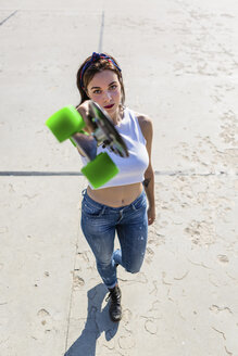Portrait of young woman standing holding up skateboard - MGIF00265