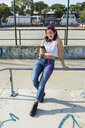 Smiling young woman with headphones and cell phone in the city - MGIF00277