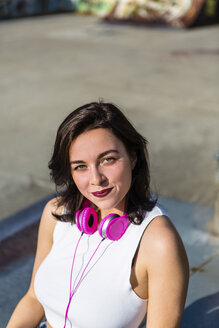 Portrait of smiling young woman with headphones in the city - MGIF00280