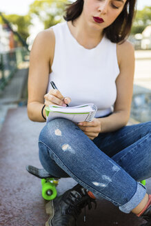 Young woman sitting on skateboard taking notes - MGIF00286