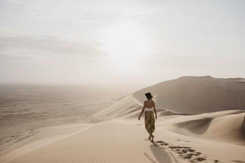 Namibia, Namib, back view of woman walking barefoot on desert dune - LHPF00260