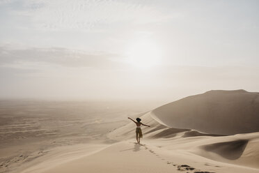 Namibia, Namib, back view of woman standing on desert dune looking at view - LHPF00263
