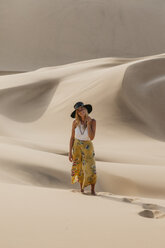 Namibia, Namib, smiling young woman standing on desert dune - LHPF00266