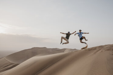 Namibia, Namib, two friends jumping in the air on desert dune - LHPF00272