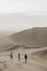 Namibia, Namib, three friends walking down desert dune - LHPF00275