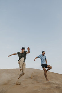 Namibia, Namib, two friends jumping down desert dune - LHPF00278