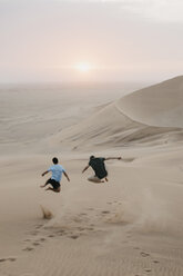Namibia, Namib, back view of two friends jumping in the air on desert dune - LHPF00284