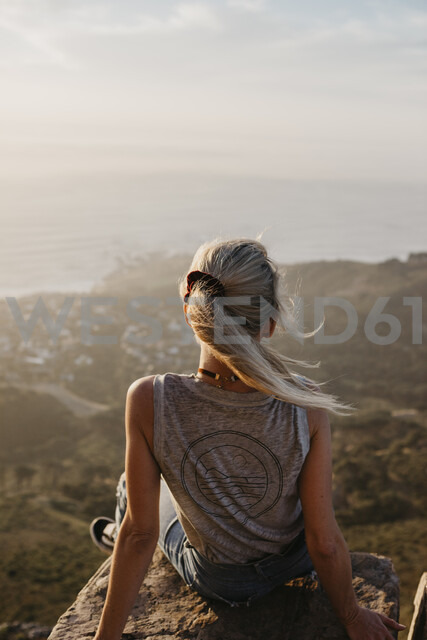 South Africa, Cape Town, Kloof Nek, woman sitting on rock at sunset - LHPF00290 - letizia haessig photography/Westend61