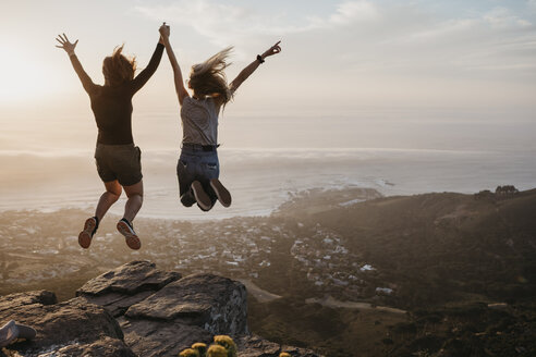 South Africa, Cape Town, Kloof Nek, two women jumping on rock at sunset - LHPF00296