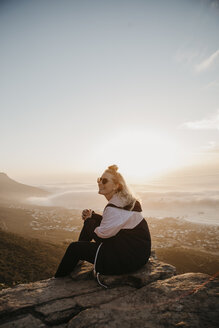 South Africa, Cape Town, Kloof Nek, smiling woman sitting on rock at sunset - LHPF00299