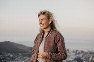 South Africa, Cape Town, Kloof Nek, smiling woman at the coast at sunset - LHPF00302