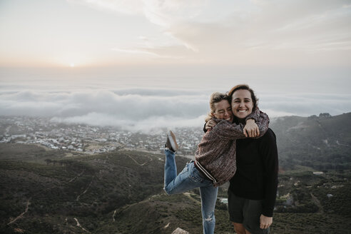 South Africa, Cape Town, Kloof Nek, portrait of two happy women embracing at sunset - LHPF00305