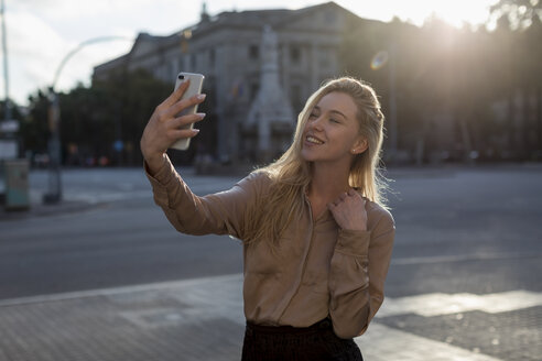 Happy young woman taking a selfie in the city - MAUF02112