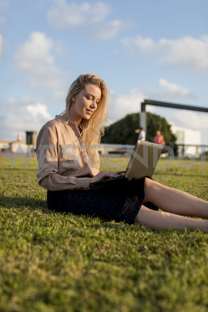 Young businesswoman sitting on a meadow using laptop - MAUF02115