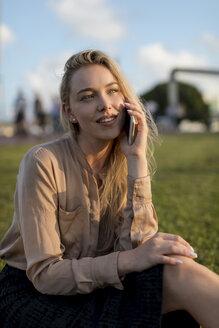 Smiling young businesswoman on cell phone on a meadow - MAUF02118