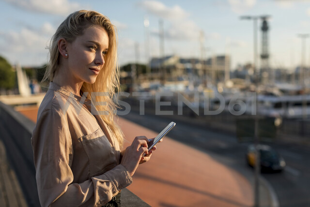 Beautiful young businesswoman with cell phone at the waterfront - MAUF02121 - Mauro Grigollo/Westend61