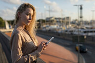 Beautiful young businesswoman with cell phone at the waterfront - MAUF02121