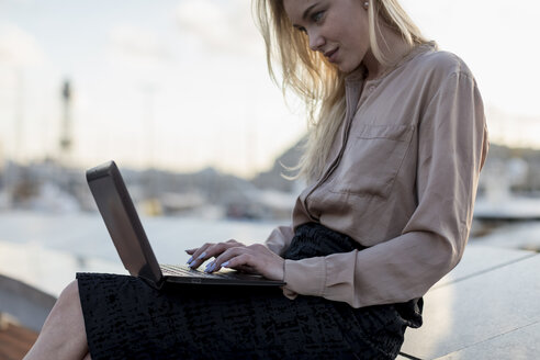 Young businesswoman using laptop at the waterfront - MAUF02124
