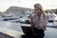Beautiful young businesswoman using cell phone and laptop at the waterfront - MAUF02127