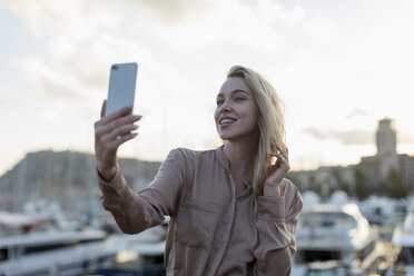 Smiling young woman taking a selfie at the waterfront - MAUF02130