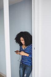 Smiling young woman using smartphone and earphones at opened balcony door - KKAF03074