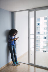 Smiling young woman standing at opened balcony door of her new appartement using smartphone - KKAF03077