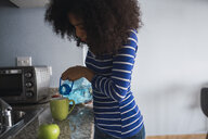 Young woman pouring water into a mug in her kitchen - KKAF03080