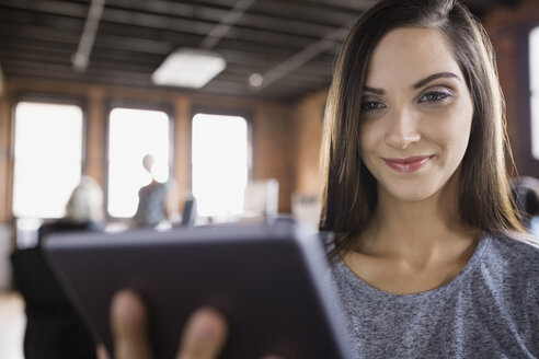 Smiling businesswoman using digital tablet in office - HEROF02349