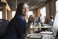 Portrait of smiling businesswoman drinking coffee in office - HEROF02355
