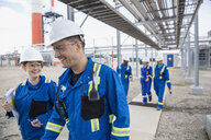 Workers walking along path at gas plant - HEROF02376