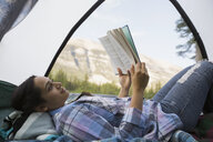 Woman reading book in tent with mountain view - HEROF02391