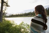 Woman wrapped in blanket looking at lake view - HEROF02421