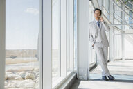 Businessman talking on cell phone at window - HEROF02538