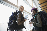 Portrait of smiling women with backpacks in airport - HEROF02643
