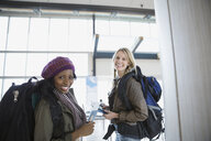 Portrait of smiling women with backpacks in airport - HEROF02649