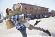 Playful couple on sunny urban street - HEROF02661
