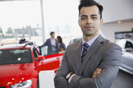 Portrait of confident salesman in car dealership showroom - HEROF02664