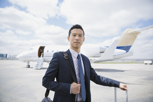 Portrait of businessman on tarmac with corporate jet - HEROF02694