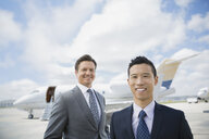 Portrait of businessmen on tarmac with corporate jet - HEROF02703
