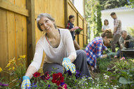 Multi-generation family planting flowers in garden - HEROF02706