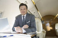 Portrait of businessman working on corporate jet - HEROF02769
