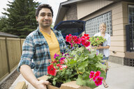 Portrait of couple unloading flowers from car - HEROF02793