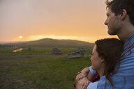 Serene couple watching sunset over rural field - HEROF02889