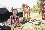 Woman holding box of apples outside truck - HEROF02925