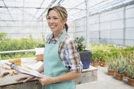Smiling worker with clipboard in greenhouse - HEROF02934