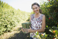 Portrait of smiling woman picking currants in garden - HEROF02943