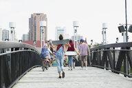 Teenagers with skateboards walking across footbridge - HEROF02964