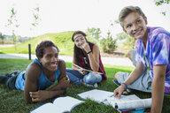 Teenagers doing homework in grass - HEROF03003