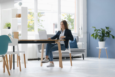 Young businesswoman sitting in office, using laptop - GUSF01674